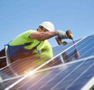 Technician connecting solar photo voltaic panel to metal platform using screwdriver standing on ladder on bright blue sky copy space background. Stand-alone solar panel system installation concept.